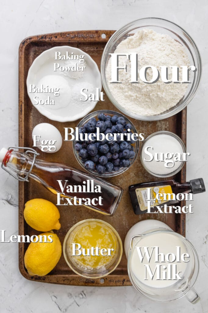 All the ingredients for lemon blueberry pancakes are arranged in glass bowls and measuring cups on a rimmed baking tray.
