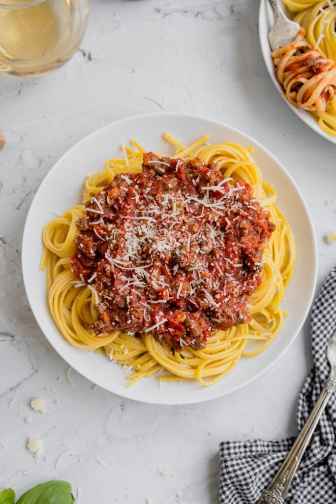 A white plate filled with cooked pasta and topped with venison meat sauce and parmesan cheese.