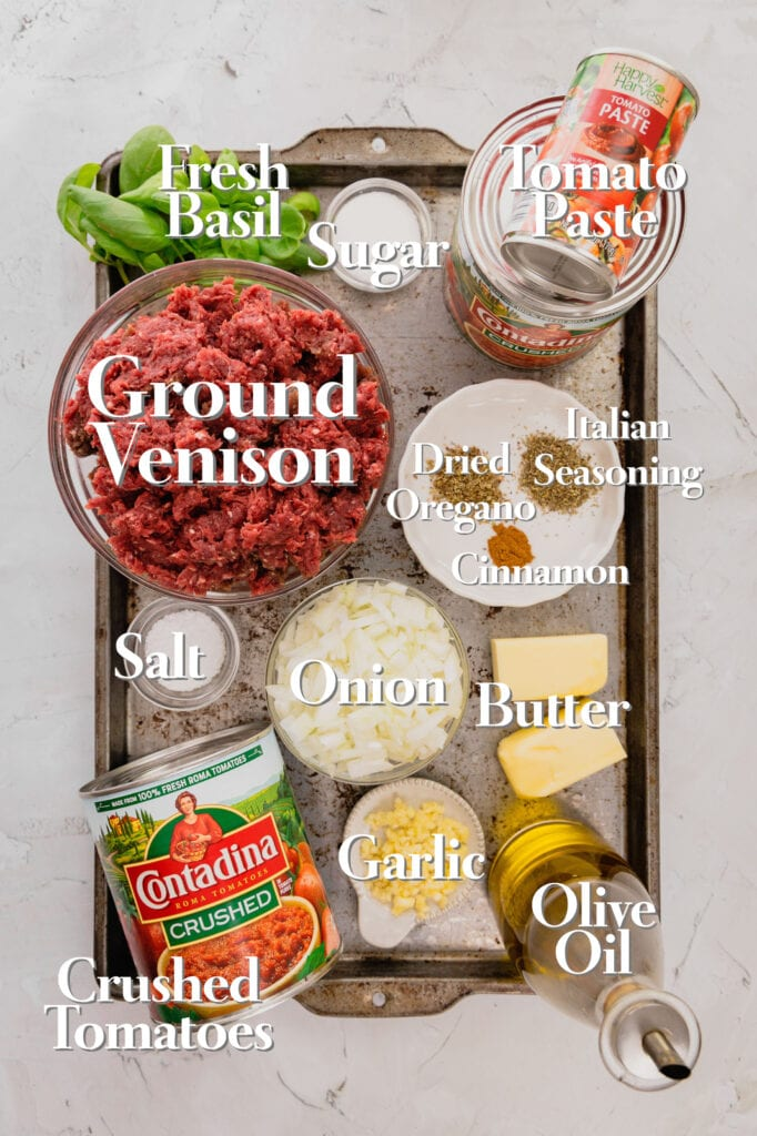 All the ingredients for venison red sauce are on a rimmed baking tray.