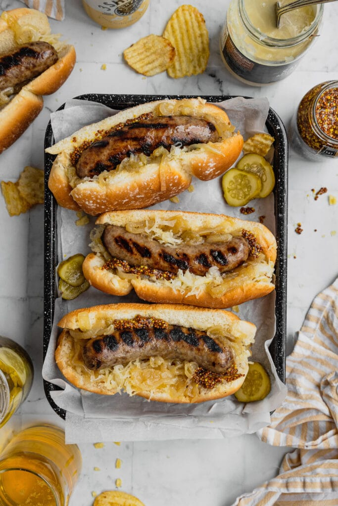 Three beer brats with onions in buns are on a black serving tray.