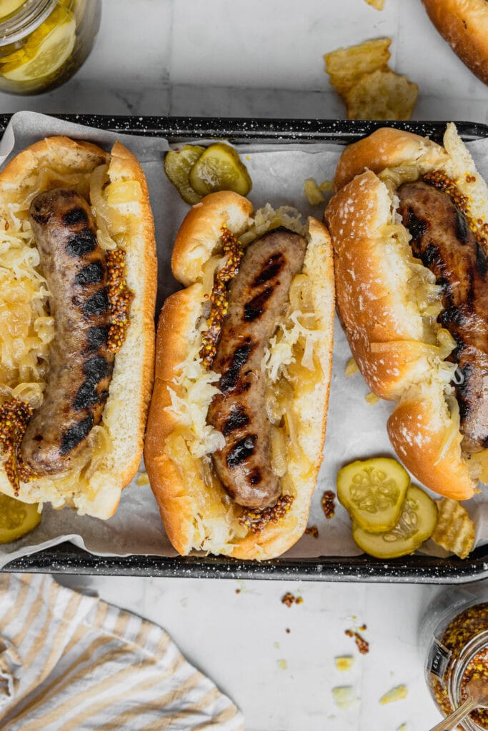 A grilled brat with onions, sauerkraut, and mustard on a black rimmed serving tray.