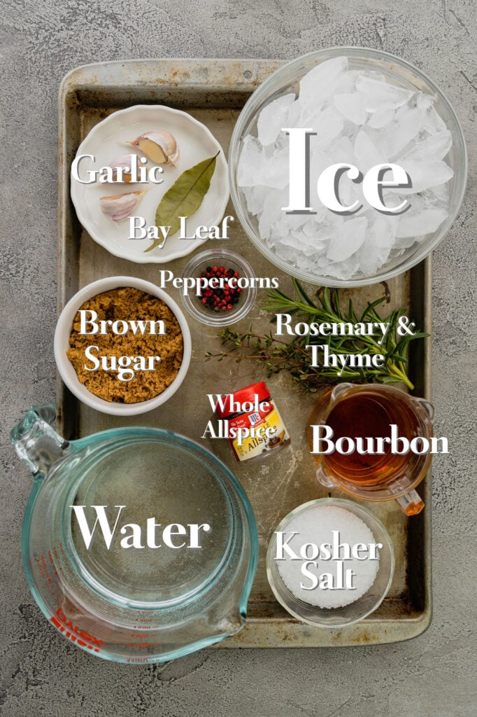 All the ingredients for brined pork chops are arranged in various glass bowls and measuring cups on a rimmed baking sheet.