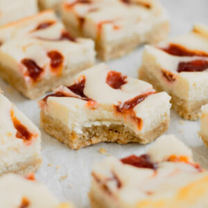 A rhubarb cheesecake bar with a bite taken out of it on parchment paper.