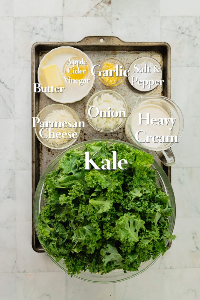 The ingredients for creamed kale are in various bowls and measuring cups on a rimmed baking sheet.