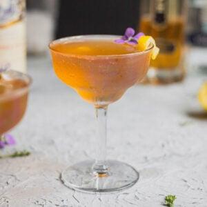 A lillet rosé martini garnished with a lemon twist