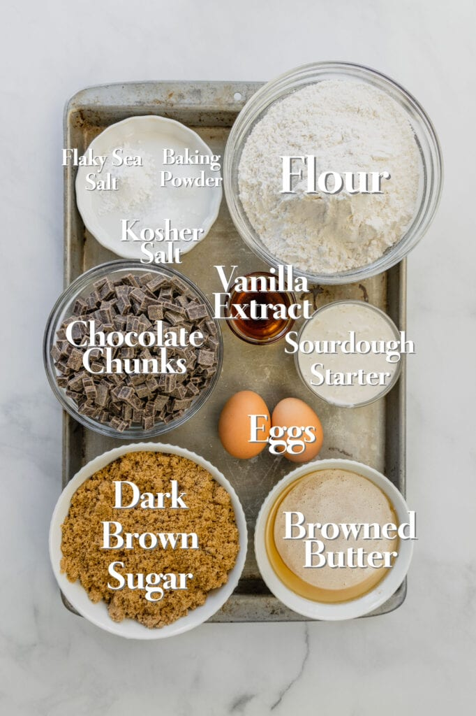 All of the ingredients for sourdough blondies are in various glass measuring bowls on a rimmed baking sheet.