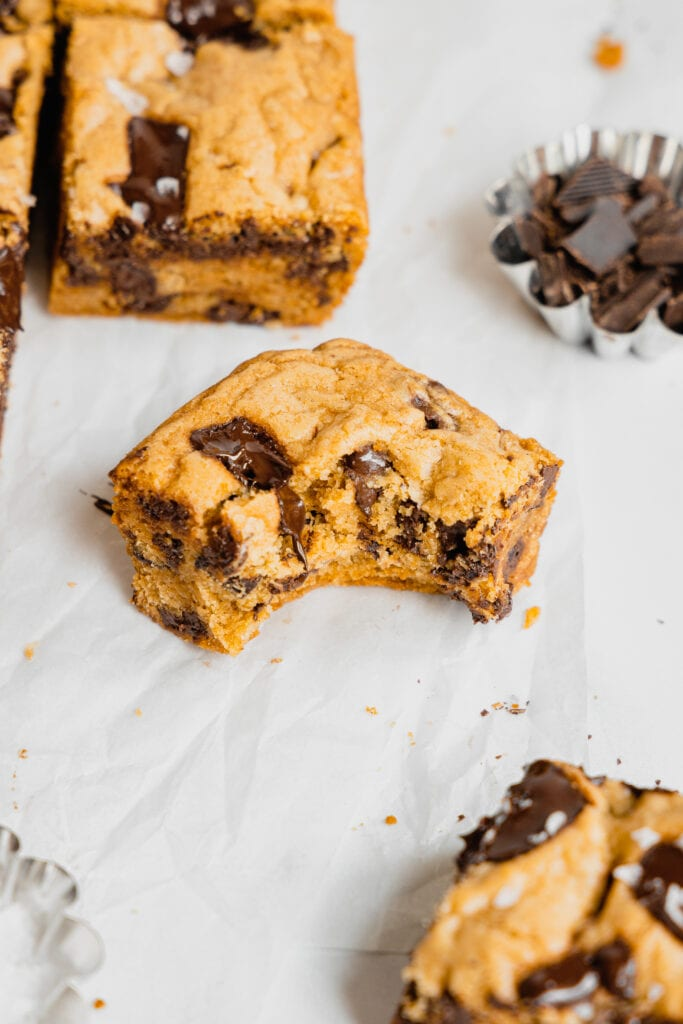 A chocolate chunk sourdough blondie with a bite taken out of it on a piece of parchment paper. There is a small silver dish full of chopped chocolate chunks in the background.