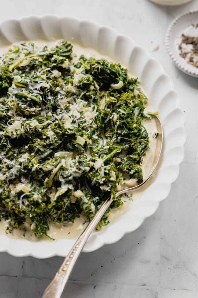A white bowl is filled with creamed kale and has a serving spoon placed inside.