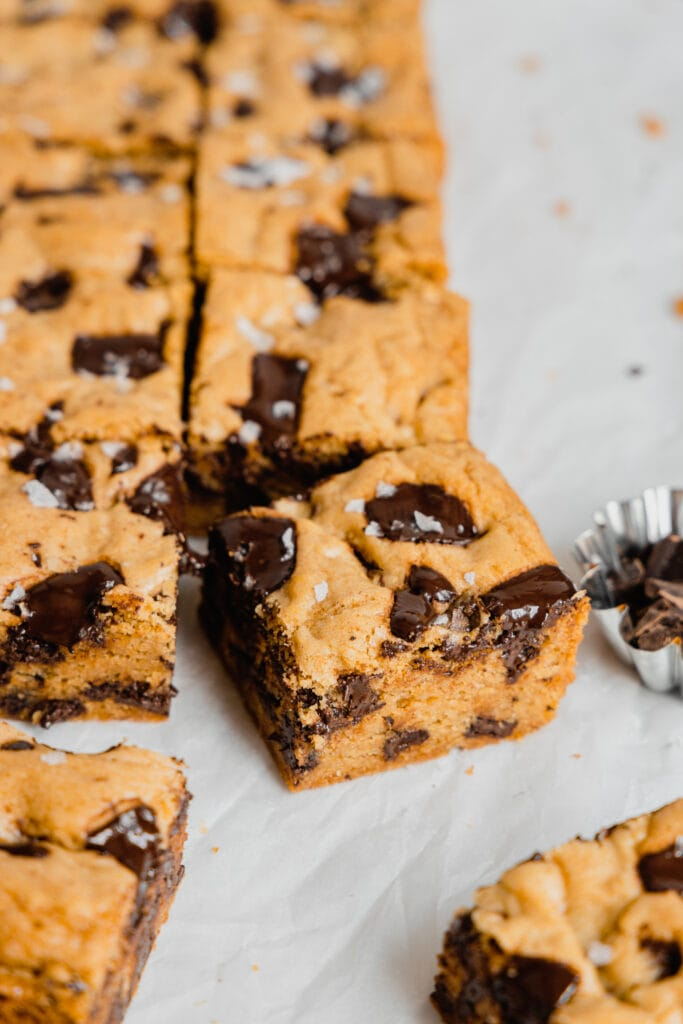 A batch of sourdough blondies with chocolate chunks and sea salt sit on a crinkled piece of parchment paper.