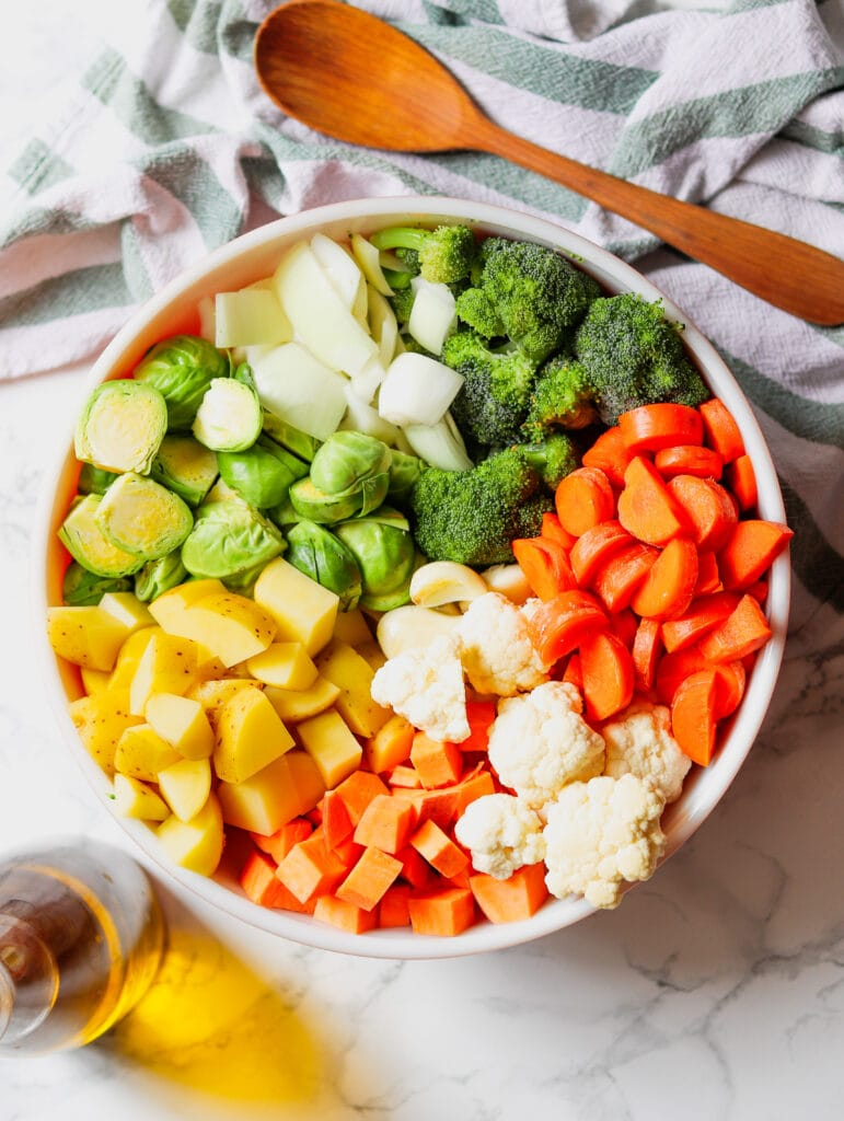 A selection of fresh vegetables are cut and in a mixing bowl.