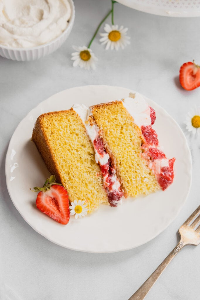 A slice of fresh strawberries and cream layer cake on a white plate.