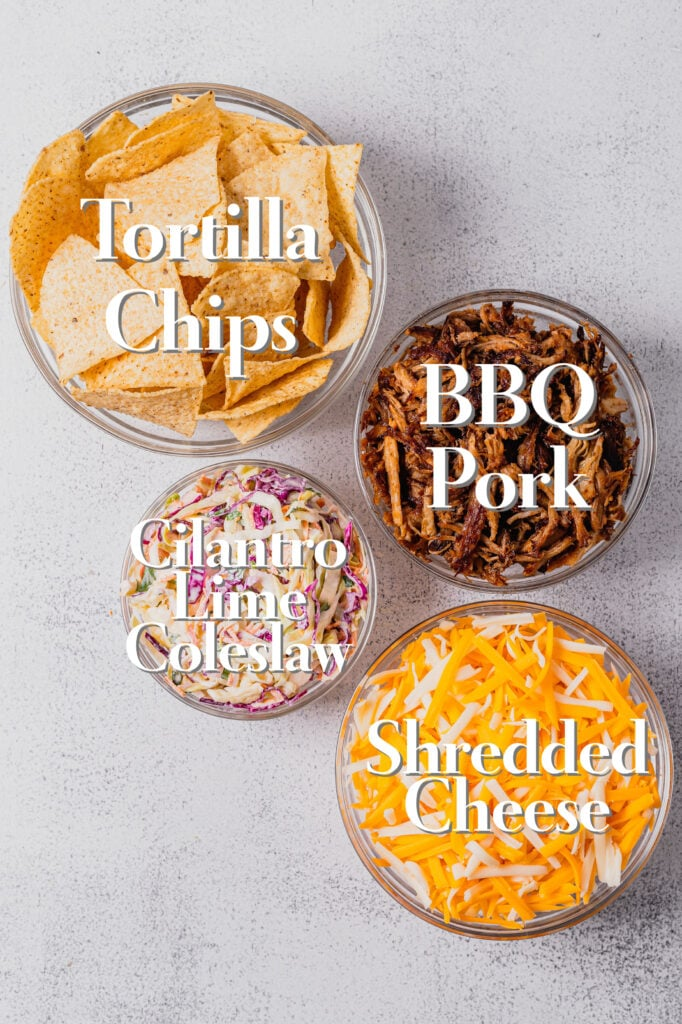 The ingredients for bbq pulled pork sheet pan nachos are arranged in glass bowls on a white backdrop.