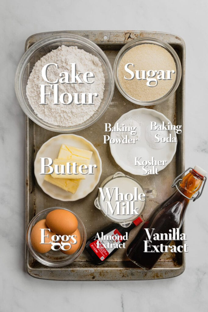 Ingredients for a simple yellow cake to make a berries and cream cake are all arranged on a rimmed baking sheet.