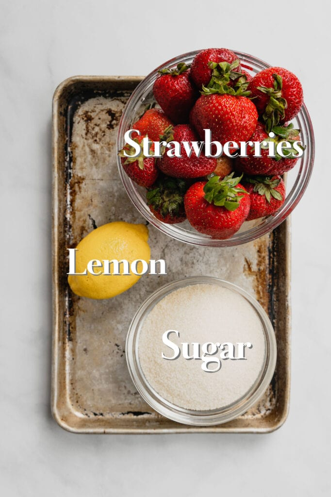 The ingredients for a simple strawberry jam sauce are arranged on a rimmed baking sheet.