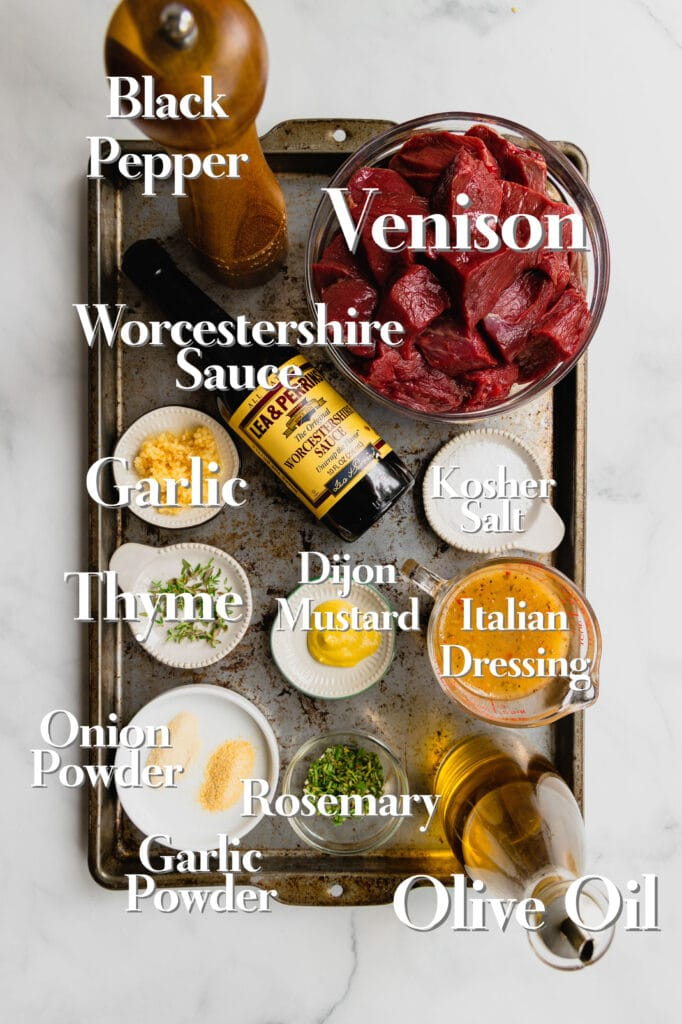 All of the ingredients for venison marinade are in various bowls and measuring cups on a rimmed baking sheet. Each item is labeled.
