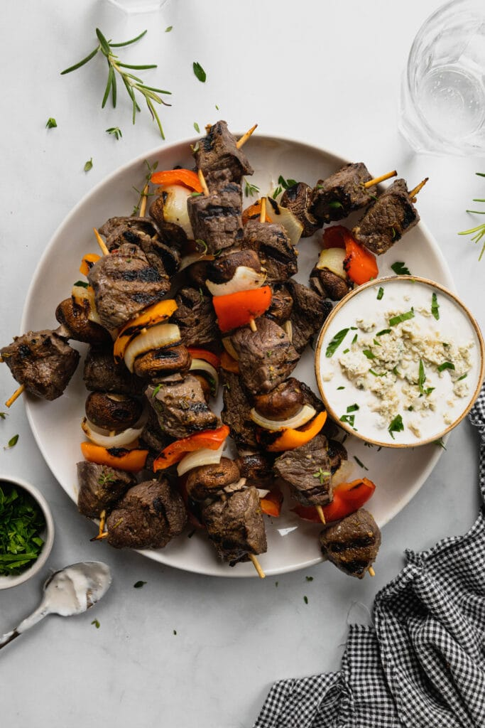 A white plate filled with grilled venison kebabs and a small dish of horseradish blue cheese dipping sauce.