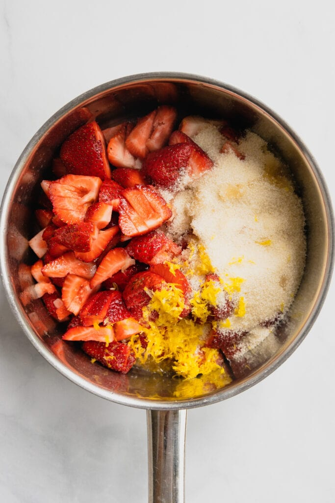 Ingredients for a quick strawberry jam are in a small sauce pot.