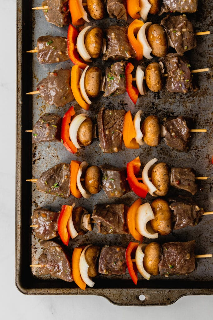 A rimmed baking sheet full of venison kebabs ready to go on the grill layered with fresh vegetables.