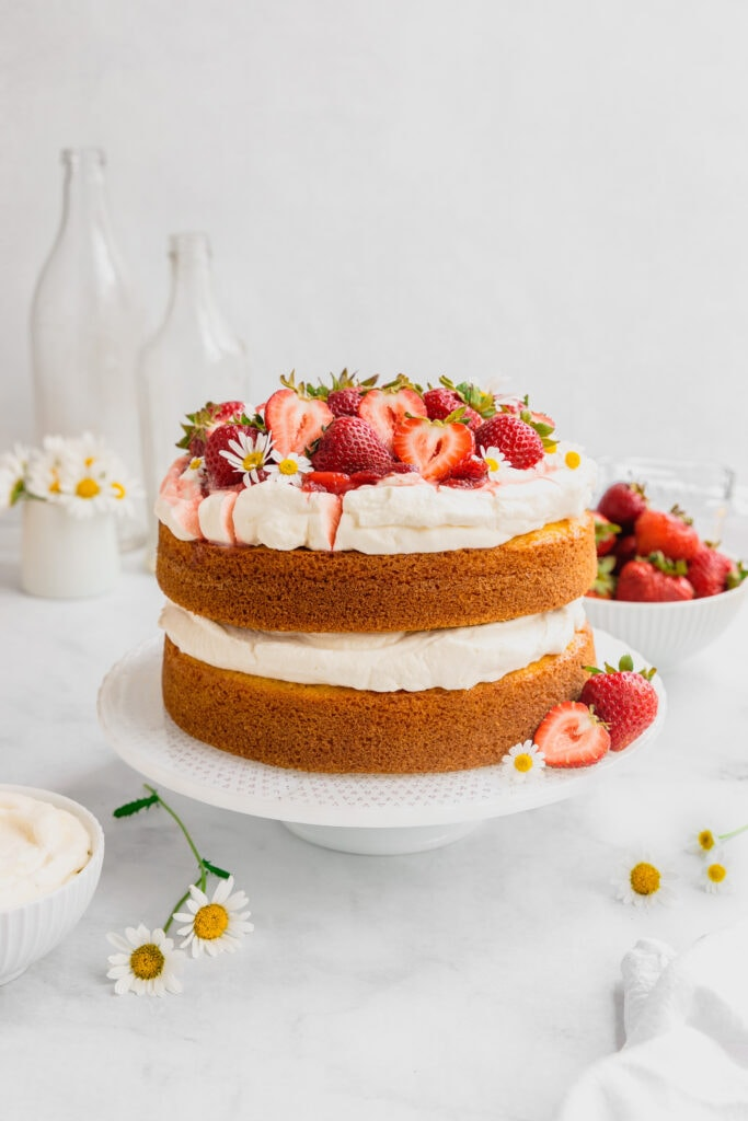 A strawberries and cream layer cake is decorated on a white cake stand with fresh berries and flowers.