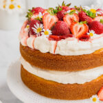 A fresh strawberries and cream layer cake on a white cake stand.