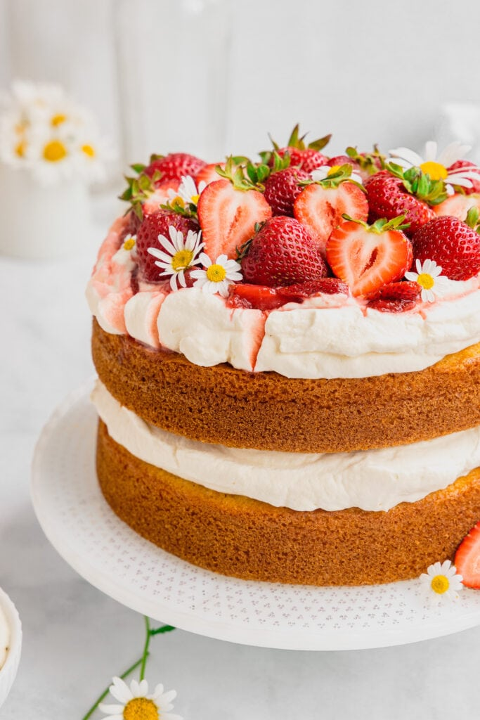 A strawberries and cream cake topped with fresh cut strawberries and flowers on a white cake stand.