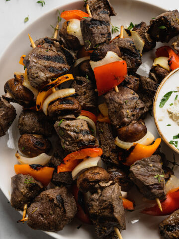 Venison kebabs after being grilled on a white serving plate