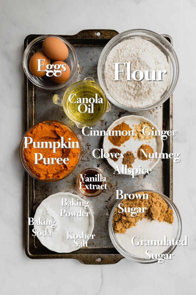 All of the ingredients for homemade pumpkin bars are arranged in various glass bowls and measuring cups on a rimmed baking sheet.