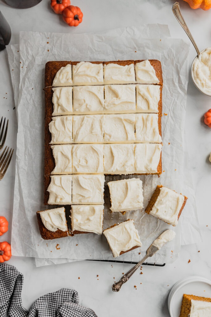 A batch of pumpkin bars topped with cream cheese frosting are cut into small squares on a piece of parchment paper.