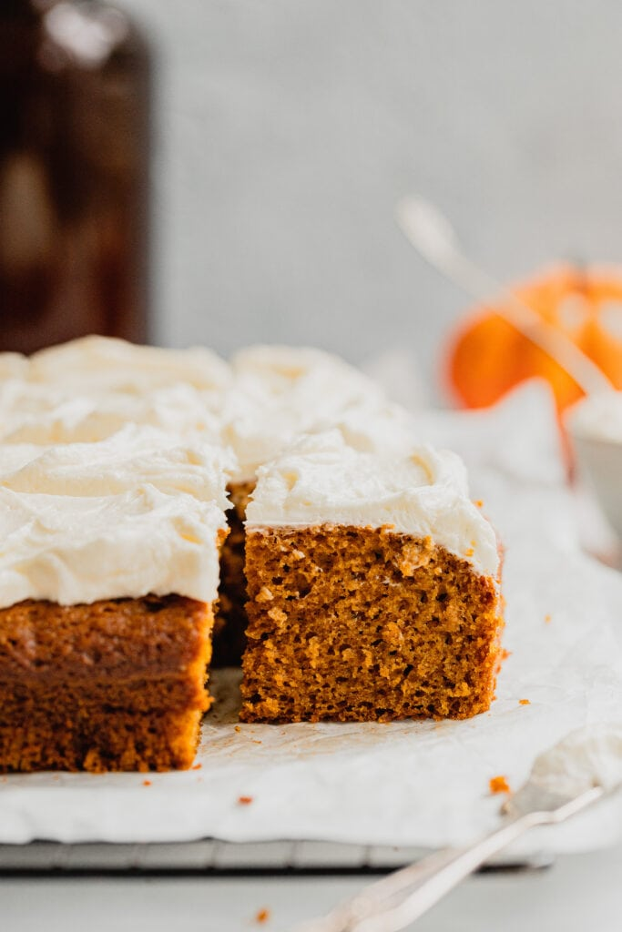 A pumpkin bar topped with cream cheese frosting on a piece of parchment paper.
