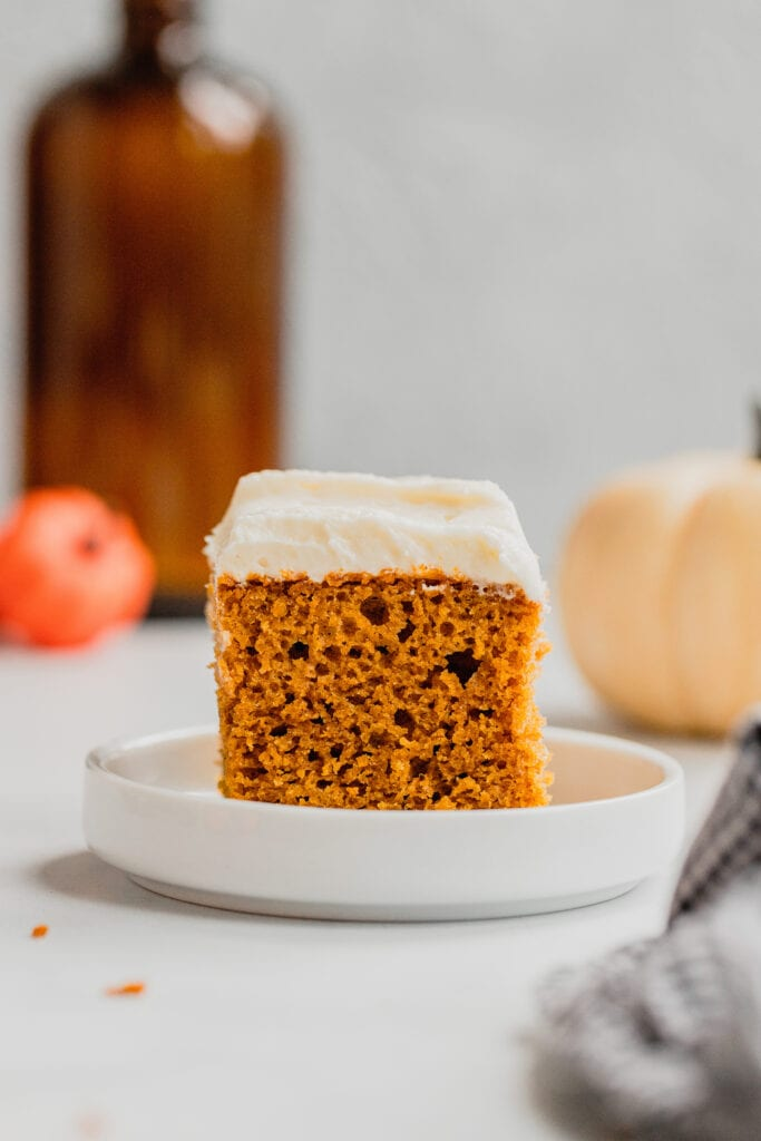 A frosted, perfect pumpkin bar sits on a small white plate.
