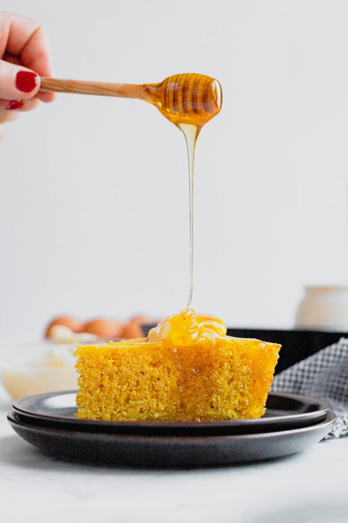 A slice of cornbread is topped with butter and drizzled with honey on a plate.