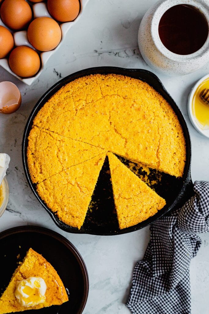 A cast iron pan filled with slices of freshly baked cornbread.