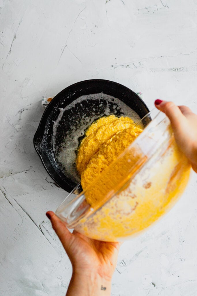 Cornbread batter is poured into a hot cast iron skillet.