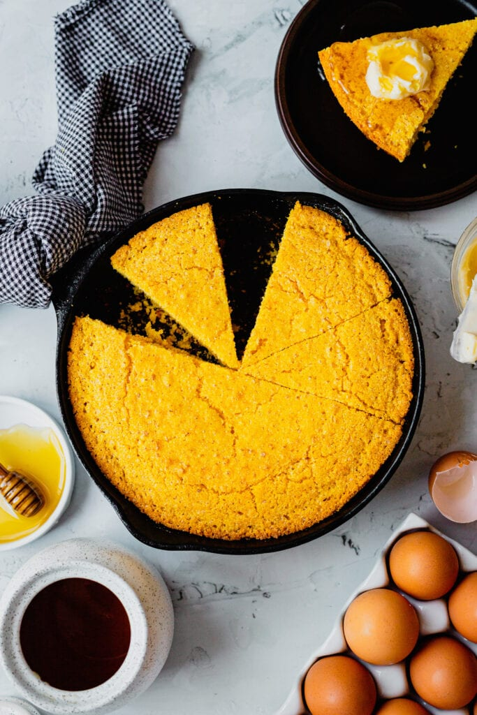 A cast iron pan filled with a batch of homemade cornbread with a slice taken out of it.